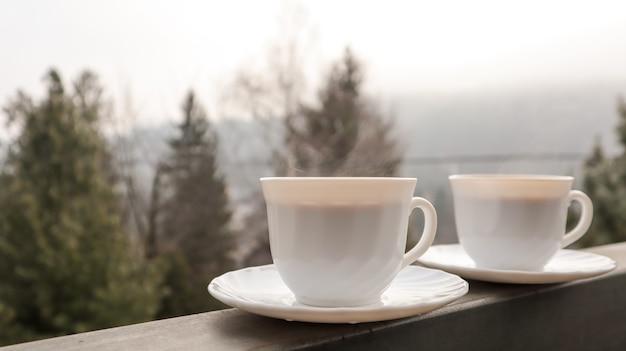 朝の山の風景とバルコニーに2つのコーヒーカップ。
