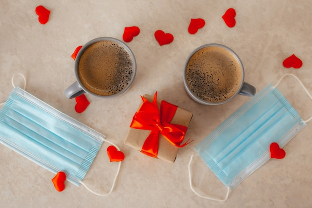 Two coffee cups on the table, next to a gift box with a red bow, medical masks, and scattered red confetti hearts. st. valentine's day in a pandemic.