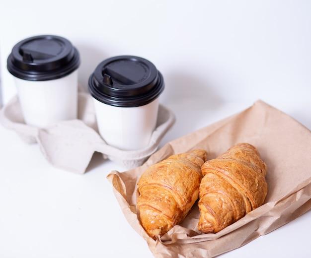 Два кофе в бумажных стаканчиках и круассаны на белом фоне