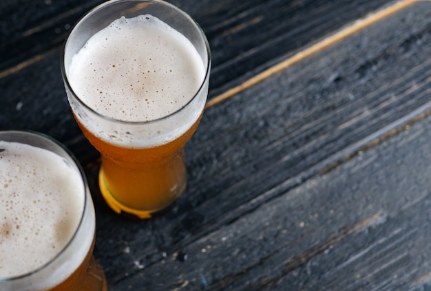 Two cold beers in a glass on a wooden table with space for text