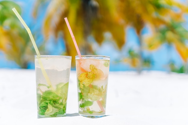 Two cold tasty mohito cocktails on the white sandy beach in palm grove