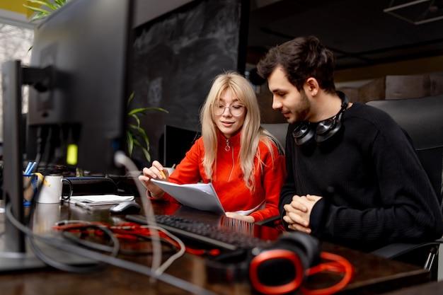 Двое коллег обсуждают вопросы в современном офисе. коллеги мужчины и женщины сидят за столом с компьютером. бизнес-план.
