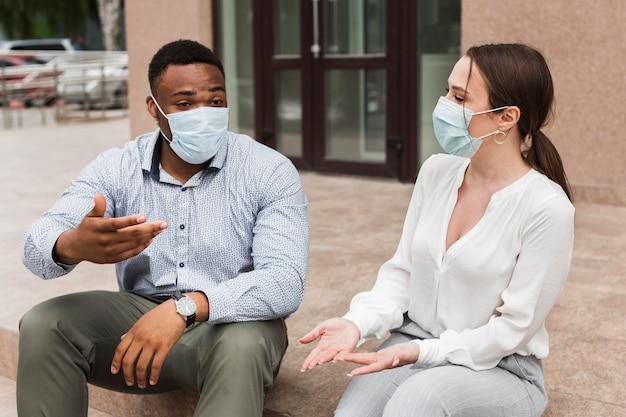 Двое коллег болтают на открытом воздухе во время пандемии в масках