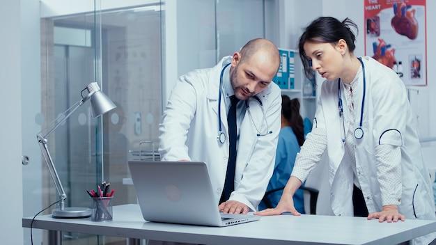 두 명의 동료 의사가 문제에 대해 상담하고 있으며, 유리벽이 있는 배경의 현대적인 개인 클리닉, 의료진과 환자가 걷는 분주한 복도. 건강 관리 시스템