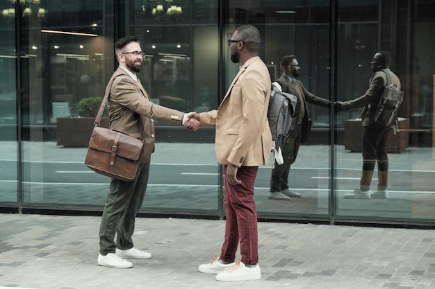 屋外の街での会議中にお互いに挨拶する2人の同僚
