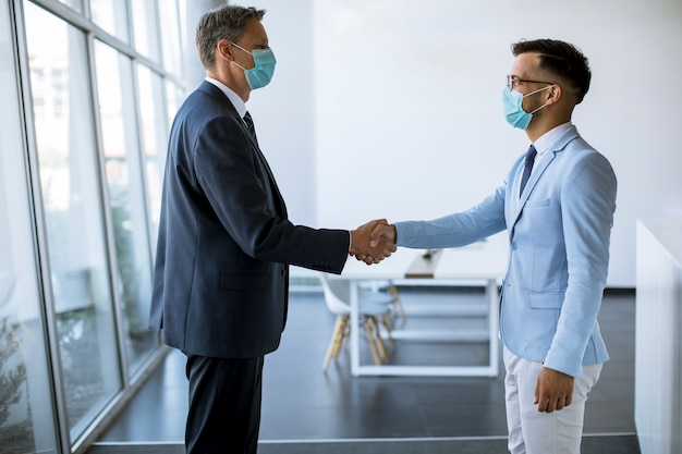 Two colleagues handshake when meeting in the office