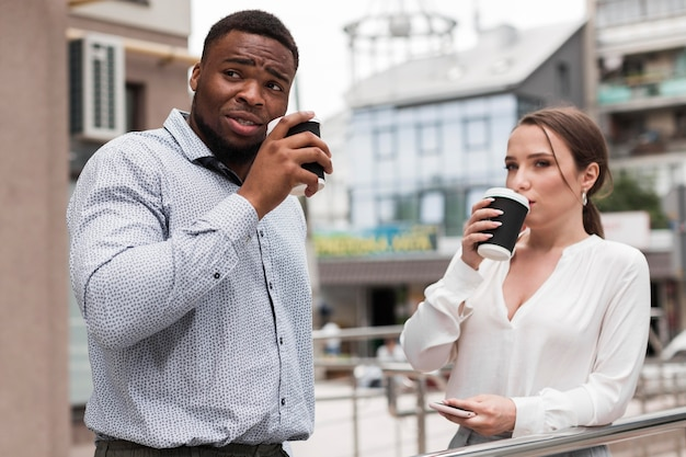 Двое коллег пьют кофе на работе во время пандемии