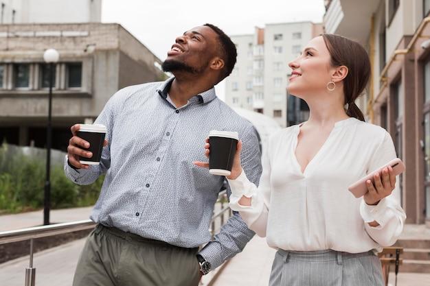 Двое коллег вместе пьют кофе на работе