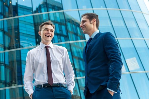 Два коллеги в костюмах разговаривают друг с другом и улыбаются перед современным зданием