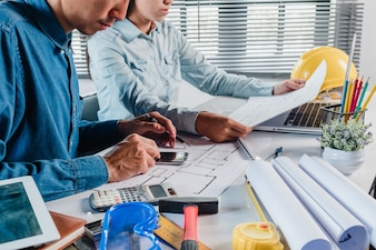 Two colleagues interior designer discussing data and calculator and computer laptop