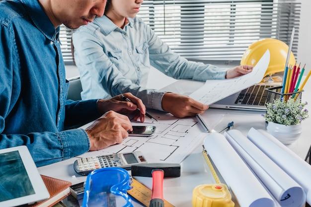 Два коллега-дизайнера интерьера обсуждают данные и калькулятор и компьютерный ноутбук