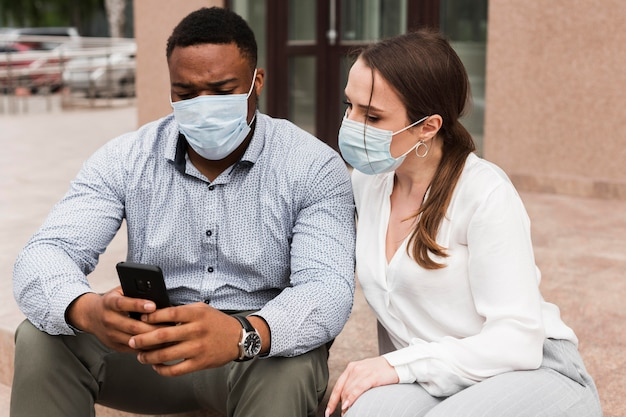 Two colleagues looking at smartphone outdoors during pandemic with face masks