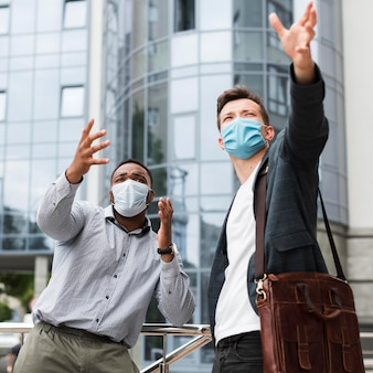 Two colleagues outdoors during pandemic wearing medical masks