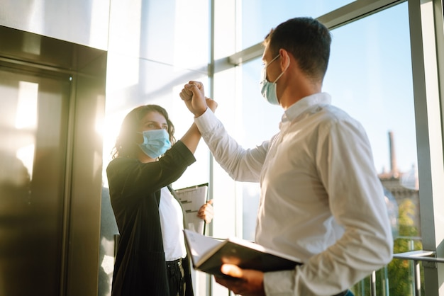 Two colleagues in protective sterile mask bumping elbows. covid-19.