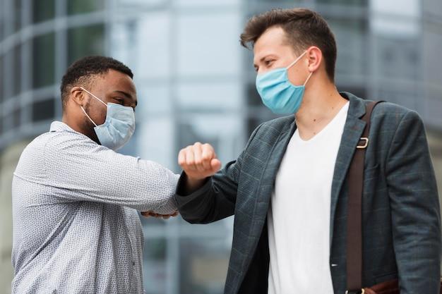 Двое коллег трогают локти на открытом воздухе во время пандемии