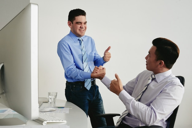 Two colleagues with thumbs up shaking hands as a sign of good job