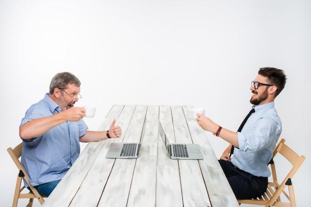 明るい灰色の背景で一緒にプロジェクトに取り組んでいる2人の同僚。彼らはコーヒーを飲みます。幸せな男と嫉妬深い男。ビジネスにおける競争の概念