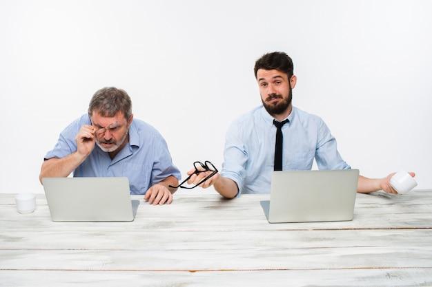 白のオフィスで一緒に働いている2人の同僚