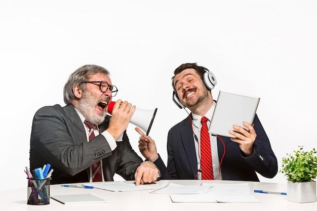 Два коллеги, работающие вместе в офисе на белом