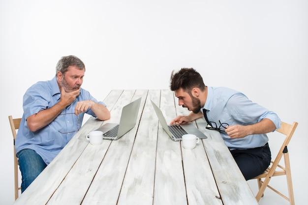 I due colleghi che lavorano insieme in ufficio su sfondo bianco. entrambi guardano gli schermi dei computer. entrambi molto turbati. concetto di emozioni negative e cattive notizie