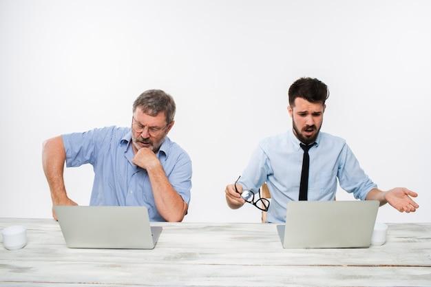 I due colleghi che lavorano insieme in ufficio su sfondo bianco. entrambi guardano gli schermi dei computer. concetto di emozioni negative e cattive notizie