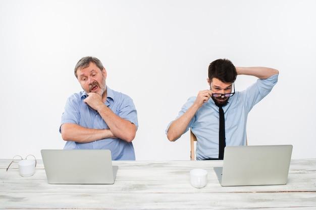 I due colleghi che lavorano insieme in ufficio su sfondo bianco