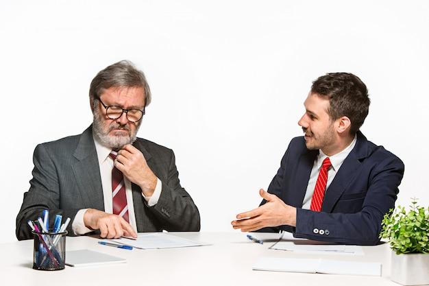 I due colleghi che lavorano insieme in ufficio su studio bianco