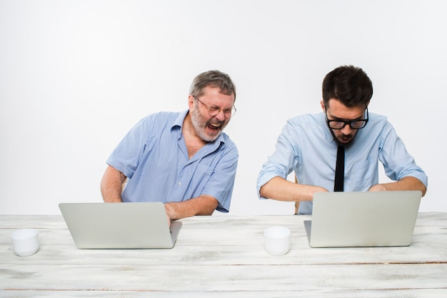 Two colleagues working together at office on white
