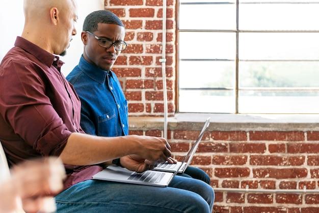 ラップトップで一緒に作業している2人の同僚
