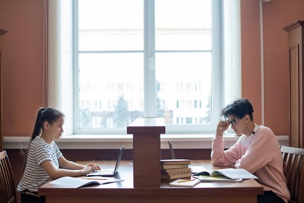 두 명의 대학생들이 책상 앞에 앉아 인터넷 서핑을하면서 노트북 디스플레이를보고 있습니다.