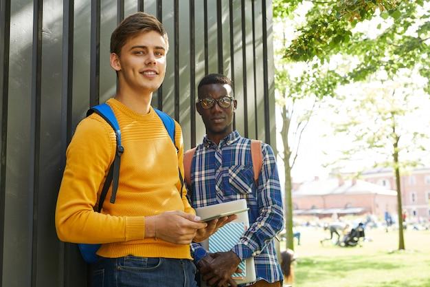 Два студента колледжа позирует в кампусе