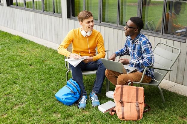 屋外で勉強する2人の大学生