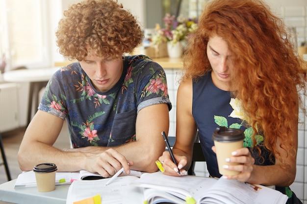 コーヒーショップで一緒に座っている巻き毛を持つ2つの大学生