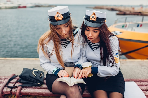 Two college women students of marine academy reading book by sea wearing uniform. friends studying