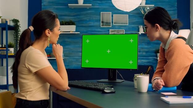 ソーシャルメディア広告用のモックアップグリーンスクリーンクロマキーディスプレイを備えたコンピューターで一緒に作業している2人の同僚