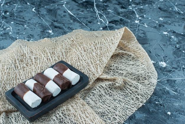 파란색 테이블에 식탁보에 나무 접시에 2 색 사탕.