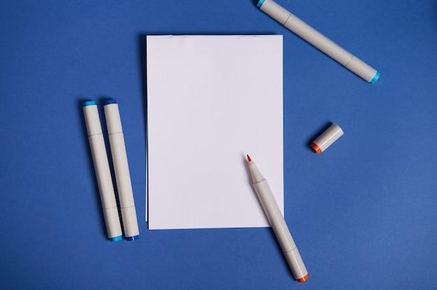 Двухцветная плоская композиция с акварельными маркерами или фломастерами с белым чистым листом бумаги с копией пространства, изолированной на синем фоне.
