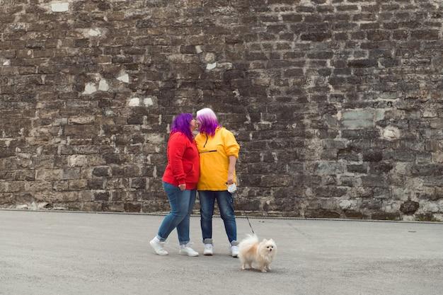 돌담 배경 도시 거리에서 작은 개가 키스하는 두 가지 색 머리 레즈비언