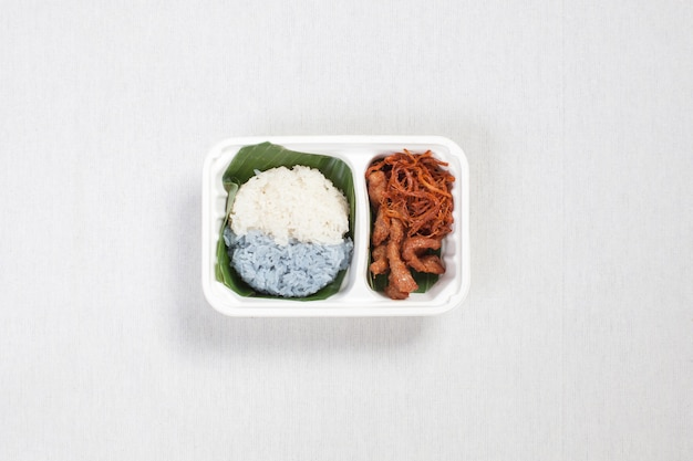 Two color sticky rice with fried pork and shredded pork put in a white plastic box, put on a white tablecloth, food box, thai food.