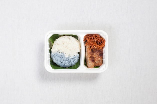 Two color sticky rice with grilled pork and shredded pork put in a white plastic box, put on a white tablecloth, food box, thai food.