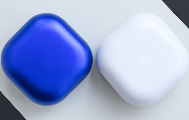 Two colored cases for wireless headphones on a white surface