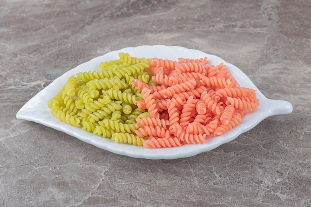Two-colored fusilli pasta in bowl , on the marble surface.