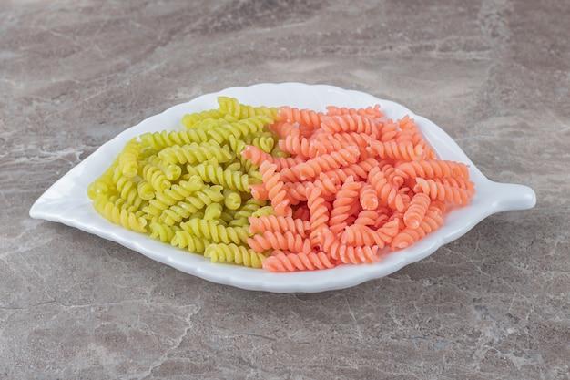 Двухцветная паста фузилли в миске на мраморной поверхности.
