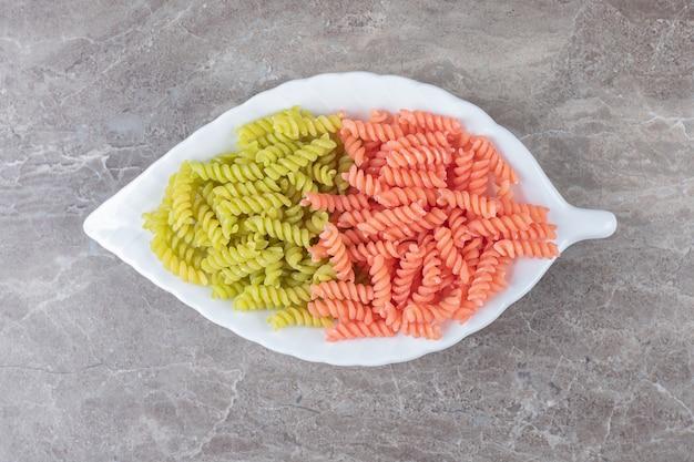 Двухцветная паста фузилли в миске на мраморе.