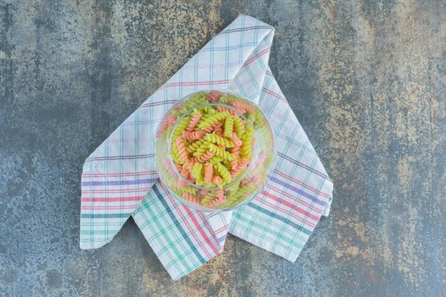 Двухцветная паста фузилли в стакане, на полотенце, на мраморной поверхности.