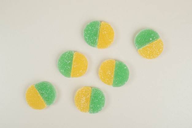 Two colored jelly candies on white surface