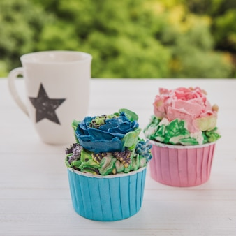 Two colored muffins with white cup with star on white wooden table with bright greens