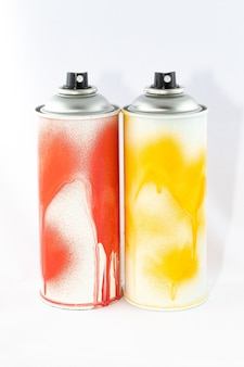 Two colored spray paint cans on white background