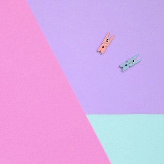 Two colored wooden pegs lie on texture background of fashion pastel violet, blue and pink colors paper in minimal concept