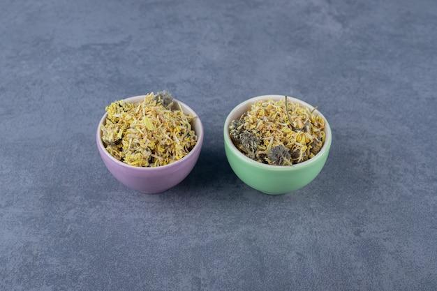 다양한 종류의 허브가 가득한 두 개의 다채로운 그릇.